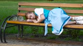 zbytky : Blond woman in bavarian costume sleeps on the bench After party mess concept.