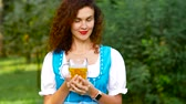 баварский : Attractive curvy haired woman in bavarian costume with beer. Oktoberfest theme. Medium shot Стоковые видеозаписи