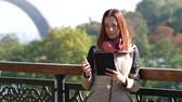 tab : Modern student with red hair using the tablet in the park. Early autumn Stock Footage