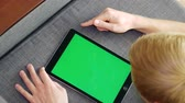 rubinetto : Young blonde man uses tablet with green screen while lying on sofa at home
