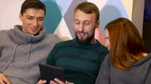 saúde : Group of people enjoy carefree time. Beardy guy shows his ipad, everybody laughs. Celebration concept