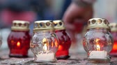 душа : Red and white candles burn on a tile. Mans hand puts a votive lamp on the background. Mourning concept. Close up Стоковые видеозаписи