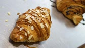 kruvasan : Pastry cook sprinkles croissant with nuts. Close up
