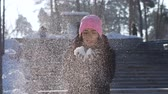 Pretty young girl pink cap blowing snow outdoors. Middle plan Vídeos