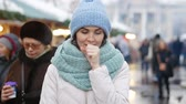 Young sick brunette with a scarf coughing outdoors