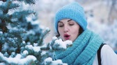 Girl blowing snow from christmas tree. Winter pastime concept