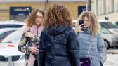 Curly girls having fun by photographing each other on the street. Young beautiful ukrainian women Vídeos