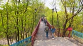 Walk on the pedestrian bridge. Bridge of lovers in Kiev. Flying over the bridge in the park