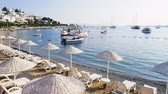 Time lapse on the coast of the resort town of Bodrum, Turkey. Umbrellas and sun beds on the beach. Yachts and boats bobbing on the waves early in the morning. Travel concept Filmati Stock