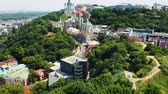Slow rising shot over bushy hill revealing Andrews descent and Andrews Church in Kiev. Famous place in Kyiv. Aerial footage 4k Filmati Stock