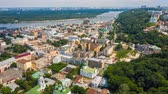 Fly over famous Kiev Podil district at summer. Kontractova square with rotating white ferris wheel. Aerial footage 4k