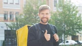 oke : Courier with a yellow bag showing thumbs up. Bearded guy with a backpack makes a gesture and smile. Delivery Service Worker 4k Stockvideo