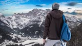 sehen : A boy looks towards the mountains covered with snow and the sky flowing in timelapse