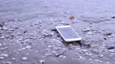 aanraken : Smartphone falls on the sand of the beach Stockvideo
