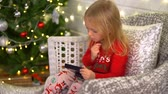 ruj : Little Girl Trying to Apply Makeup near the Christmas Tree Stok Video