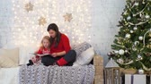 fadas : Mother and Daughter Reading a Book in Christmas