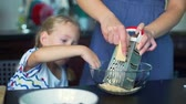assistente : Mother Grating Cheese with Daughter