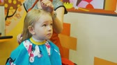 divat : Little Girl Having Haircut Stock mozgókép
