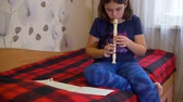 flauta : Girl Sitting on the Bed and Playing Flute