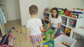 bałagan : Little Boy Helping Mother to Clean Room from Toys