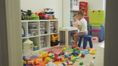 ceruza : Cute Baby Girl and Boy Drawing in Messy Room Stock mozgókép