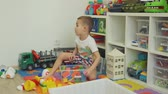ev işleri : Little Boy Organizing Toys in his Room