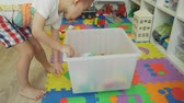 oturma odası : Little Boy Picking Up Toys after Playing at Home Stok Video
