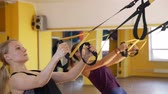 подвесной : Women Exercising with Suspension Straps in Gym