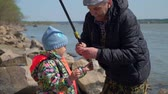 pescador : Elderly Man Giving Freshly Caught Fish to a Young Girl. Grandfather and Granddaughter are Fishing in a Spring Sunny Day. The Concept of Fishing and Leisure Activity in Nature.