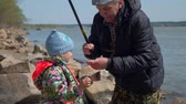 pescador : Senior Man Giving Freshly Caught Fish to his Granddaughter. Grandfather and Granddaughter are Fishing in Spring Sunny Day. The Concept of Fishing and Leisure Activity in Nature. Slow Motion