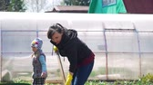 ancinho : Young Woman Digging the Soil with Shovel in the Vegetable Garden for Planting Potatoes in Slow Motion. Greenhouse on the Background. Agriculture and Tough Work Concept