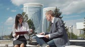 Businessman and Businesswoman Discussing Financial Data and Graphs Outdoors during Lunch Break. Slow Motion. Business, People, Paperwork Concept