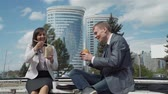 Businessman and Businesswoman Sitting on a Bench in a City and Eating Lunch Outside Office. They are Smiling and Chatting. Lifestyle and Business Concept Wideo