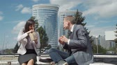 Business People Eating Junk Food in a Lunch Break Outdoors. They are Smiling and Chatting in Sunny Weather. Slow Motion. Lifestyle and Business Concept Wideo