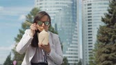 Businesswoman Eating Chinese Noodles during her Lunch Break in Slow Motion. Young Woman in Business Suit Eating Junk Food Outdoors. Lifestyle and Business Concept