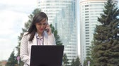 Businesswoman Talking on Phone while Using Laptop. Young Woman Wearing Business Suit Working Outdoors. Slow Motion. Lifestyle and Business Concept