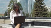 coffee break : Businesswoman Typing an Email to her Business Partner in Slow Motion. Young Woman Using Laptop Outdoors. Lifestyle and Business Concept