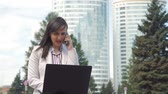 coffee break : Young Woman Talking on Phone while Using Laptop. Businesswoman Working Outdoors. Slow Motion. Lifestyle and Business Concept Stock Footage