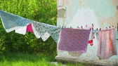 Clothes Hanging on the Clothesline Outdoor Near Run Down House. Wash clothes on a rope with clothespins. Housework and Housekeeping Concept