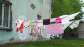 бедность : Clothes Hanging on a Clothesline in the Yard in a Disadvantaged Area. Lots of Baby Laundry in the Breeze on a Rope with Clothespins