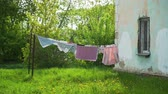 Clothes Hanging and Dressed to Dry Outdoors on the Clothesline in Spring Time. Rope with Clean Clothes on Laundry Day. Housework and Housekeeping Concept 動画素材