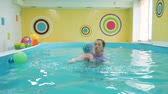 Little Baby Learning to Swim in the Pool. Swimming Lessons for Children. Trainer in Swimsuit Holding Baby in her Arms. Healthy Lifestyle and Early Development Concept Wideo
