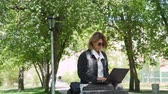 Middle Age Woman Freelancer Distantly Working in a City Park. Female Using Laptop Computer for her Work Outdoors. Freelance Work, Business People Concept 動画素材