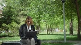 Mature Female Freelancer Working Outdoors in Sunny Day. Woman Using Laptop Computer for Distance Job in a City Park. Freelance Work, Business People Concept 動画素材