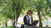 Mature Woman Sitting at a Bench in a City Park and Using Laptop. Female Freelancer Using Laptop Computer for her Work. Slow Motion. Freelance Work, Business People Concept Wideo