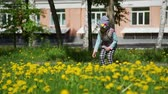 toplamak : Little Girl Collecting a Dandelions Bouquet and Walking in City Park in Spring Time. Slow Motion. People, Children, Childhood Concept Stok Video