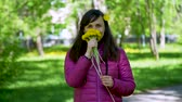 pampeliška : Beautiful Young Woman Sniffing Yellow Dandelions in a City Park in Spring Sunny Day. Woman Holding Spring Flowers in her Hands. Harmony with Nature, Concept of Vacation, Summer Leisure, Ecology Dostupné videozáznamy