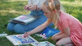 malarz : Child drawing with watercolor with Teacher Outdoors. Little Girl Attending Painting Workshop in a Park. Slow Motion. Development of Childrens Artistic Creativity and Thinking