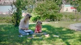ressam : Little Girl with Teacher at Painting Lesson Outdoors. Watercolor Paint with Teacher in Nature. Creativity Inspiration Expression Concept Stok Video