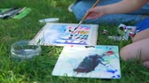 ressam : Close Up of Little Girl Drawing in Nature with Teacher. Art School Classes in the City Park. Slow Motion. Creativity Inspiration Expression Concept Stok Video